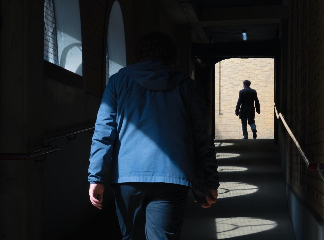 Man in blue jacket spying.