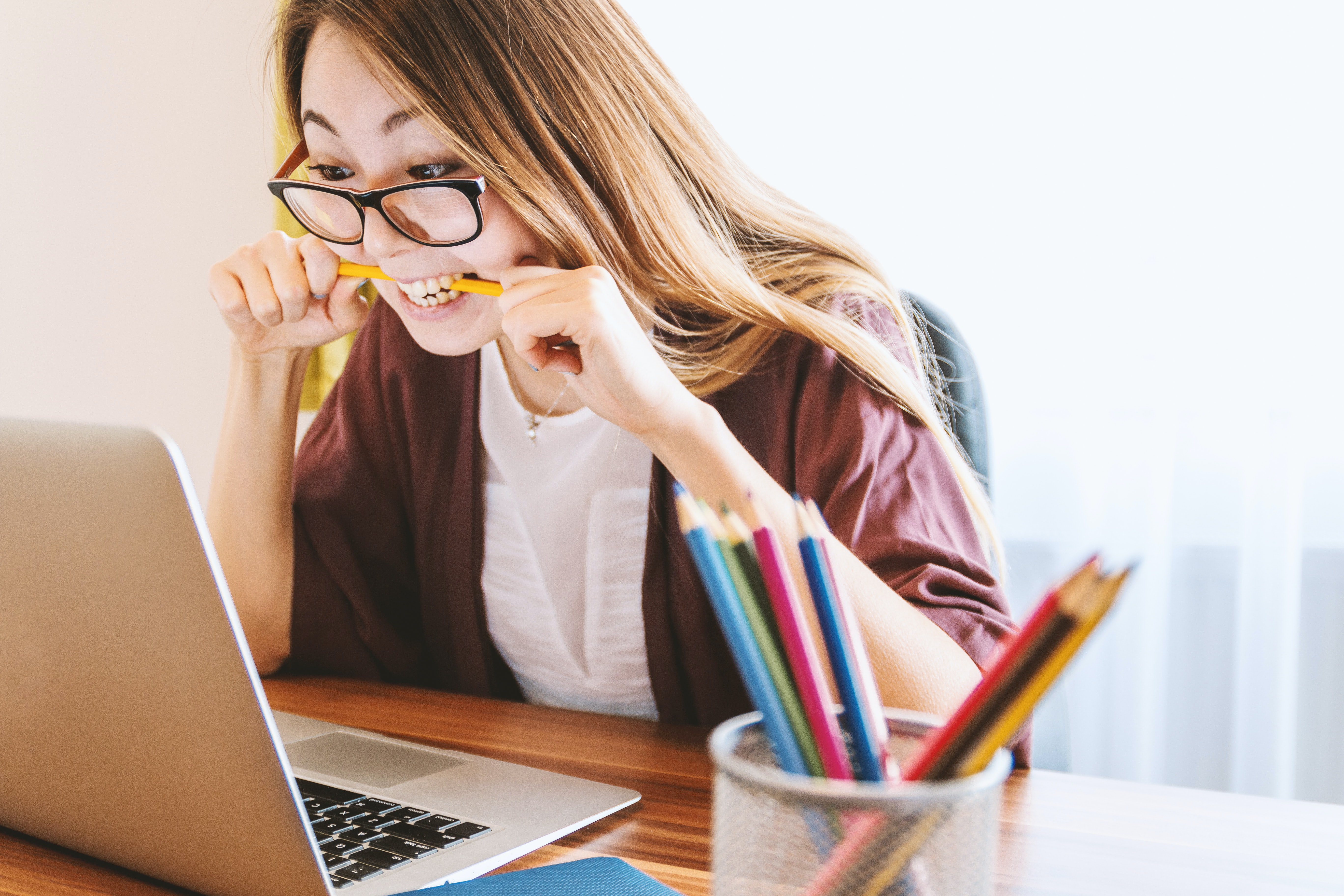 woman-biting-pencil-in-front-of-macbook