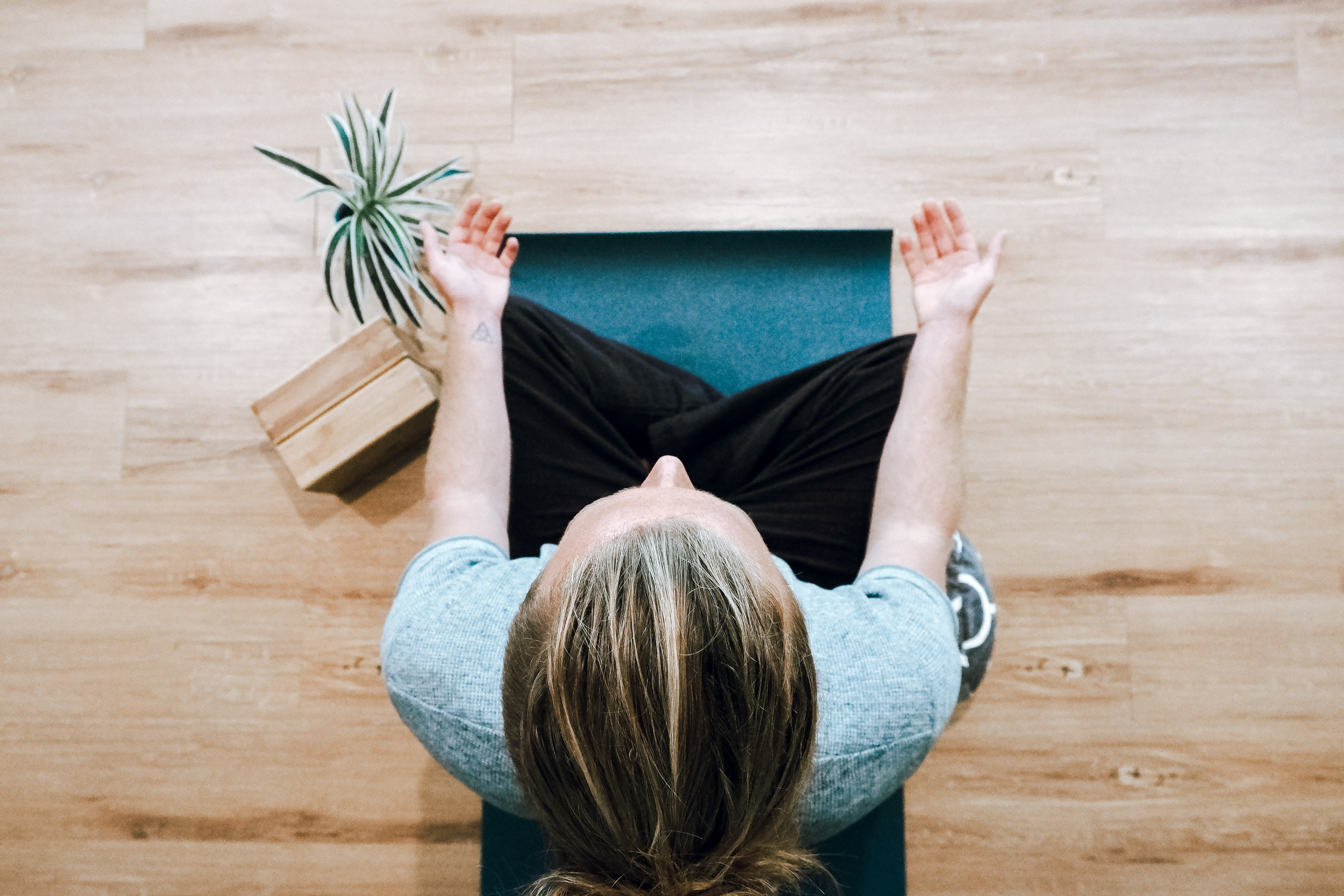 woman-in-black-pants-and-gray-shirt-sitting-in-a-wooden-floor